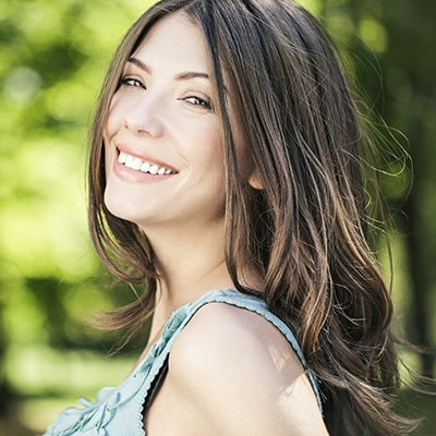 A woman turning to the camera and smiling to show how veneers, which are offered under our cosmetic dentistry in Kennesaw, GA, can enhance your smile
