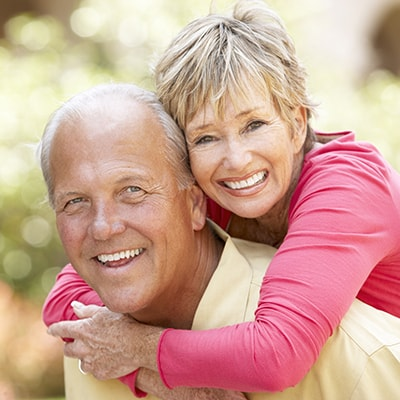 An older couple smiling to show how dentures can fix your smile.