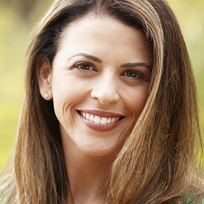 A woman smiles to show how dental implants can restore your smile.