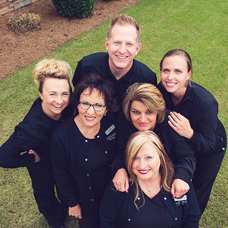 Your dentist in Kennesaw, GA, Dr. Eric Duncan and his awesome team looking up into a camera