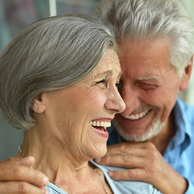 An older smiling couple shows how bridges can restore your smile