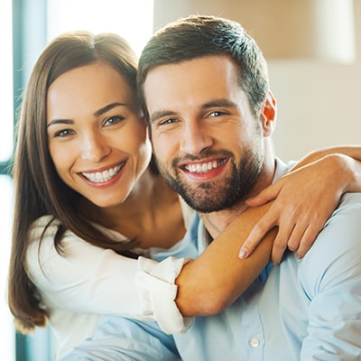 Image of a smiling couple with great smiles thanks to gum contouring.