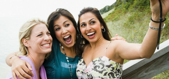 Three women smiling confidently for a selfie because they received cosmetic dentistry services from Dr. Eric Duncan at Brookpointe Dental