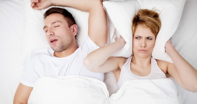 Man and woman in bed, man sleeping with mouth open and woman covering her ears with a pillow.